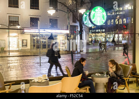 Young women at a Starbucks coffee shop. Helsinki, Finland - Stock Photo