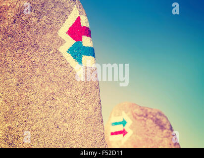 Vintage toned trail signs painted on rock, choice or dilemma concept. - Stock Photo