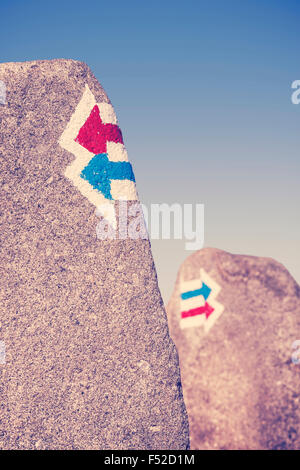 Retro toned trail signs painted on rock, choice or dilemma concept. - Stock Photo