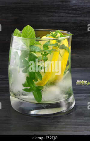 Homemade mojito cocktail in a curved glass on against dark background - Stock Photo