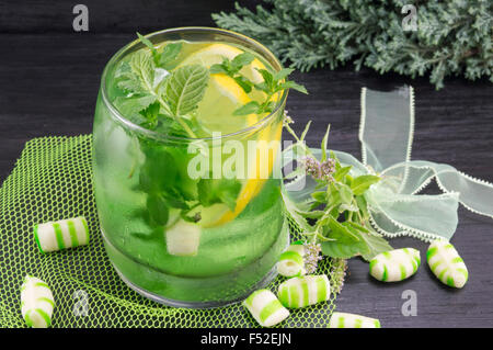 Homemade mojito cocktail in a crooked glass with mint bonbons - Stock Photo
