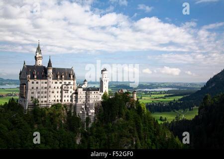 Neuschwanstein Castle overlooks the rolling hills in Bavaria, Germany. - Stock Photo