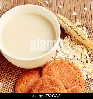 closeup of a cup with oat milk, an ear of wheat, some rolled oats and some digestive cookies on a rustic wooden - Stock Photo