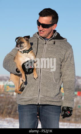 Man holding Bugg dog in city park (cross between Boston Terrier and Pug)