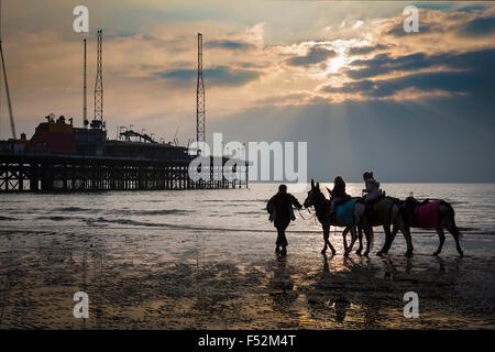 Children having a donkey ride on Blackpool beach near to the South Pier with a setting sun creating sun rays - Stock Photo
