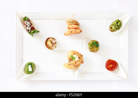 A top view of a platter with a selection of Canapes, isolated on white - Stock Photo