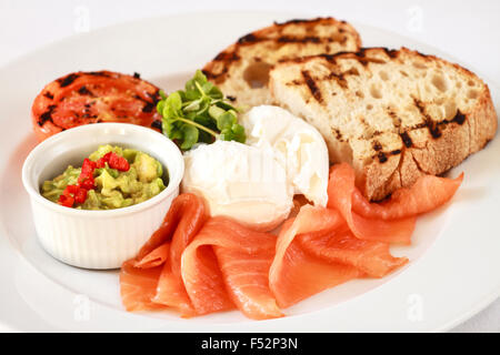 Smoked salmon with poached eggs, chilli & avocado, tomato, watercress and  slice of sourdough toast - Stock Photo