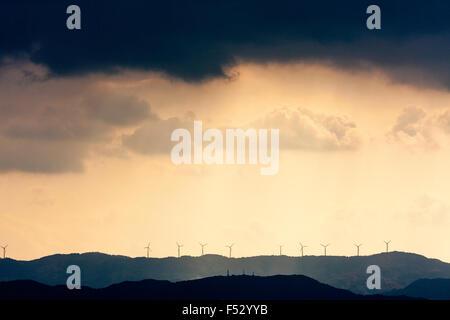Wakayama, Japan, silhouetted wind turbines in sunlight on top of mountain against yellow sky, above, very dark rain storm rain clouds.