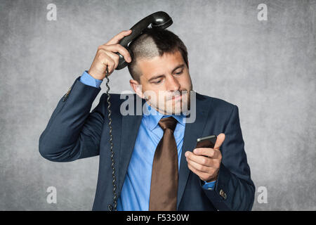 businessman with a funny haircut can not handle phone - Stock Photo