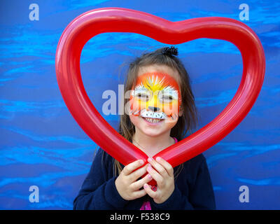 Little child (girl age 5-6)  with lion face painting  holding balloon in a shape of heart - Stock Photo