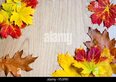 frame of autumn leaves on wooden floor - Stock Photo