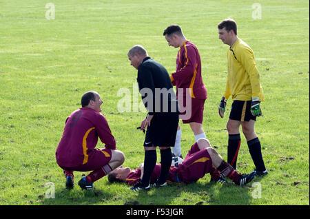 Sunday League football, injured player lying on the ground - Stock Photo