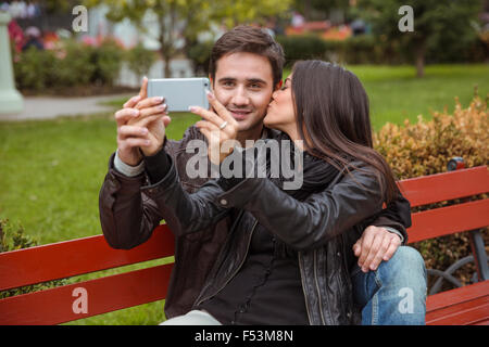 Portrait of a happy couple making selfie photo on the bench outdoors - Stock Photo