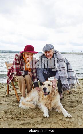 Happy senior couple with their dog resting on beach - Stock Photo