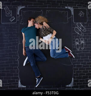 Young couple feeling relaxed in a bed drawed by chalk on paper. - Stock Photo