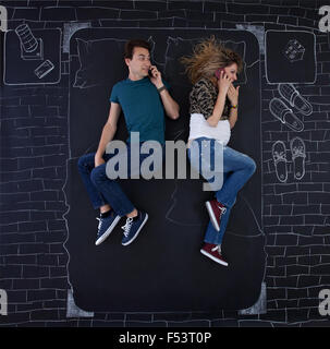 Young couple talking on the phone in bed. - Stock Photo