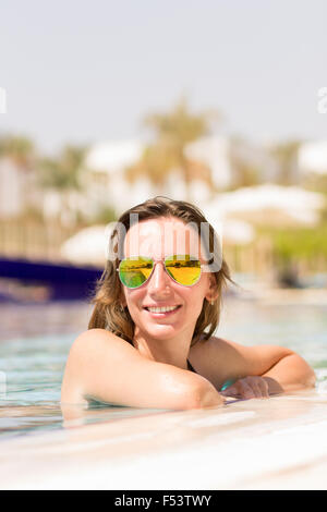 Gorgeous caucasian woman enjoying summer vacation relaxing in swimming pool. Happy girl in sunglasses at the tropical hotel reso