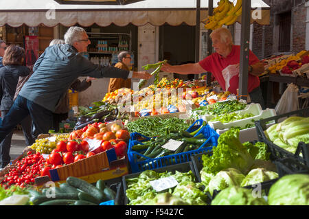 Shopping for fruit and vegetables at the Erberia the vegetable part of Mercato di Rialto, Venice, Italy - Stock Photo