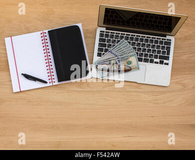 Business background, view from above on a wooden table - a laptop, notebook and pen, business card holder and dollar - Stock Photo