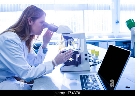 Scientist working with a microscope in laboratory - Stock Photo