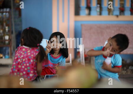 Girl in focus showing victory sign to other girl, a little boy trying to mimik her - Stock Photo