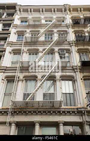 Old building in Manhattan, New York City with steel external fire escape staircase on the outside wall - Stock Photo