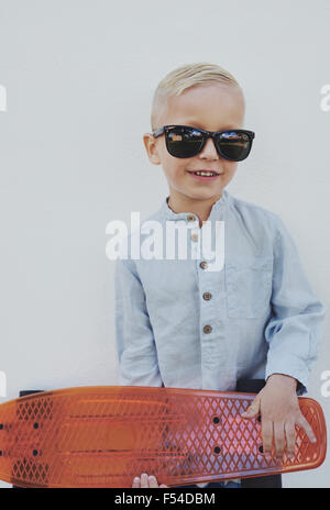 Little boy in trendy over sized sunglasses borrowed from a parent standing clutching a skateboard looking at the - Stock Photo