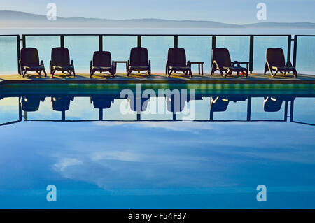 A line of chairs at an outdoor swimming pool - Stock Photo