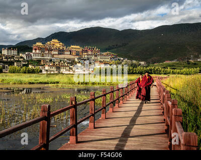 Monks in front of the Ganden Sumtseling Monastery, also known as Sungtseling and Guihuasi is a Tibetan Buddhist - Stock Photo