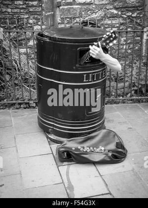 Busker sings in a litter bin, Cambridge, United Kingdom - Stock Photo