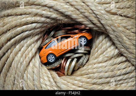 MODEL CAR WRAPPED IN ROPE WITH MONEY RE CARS MOTORING COSTS PRICES NEW CAR BUYERS BUYING SERVICING INSURANCE MONEY - Stock Photo