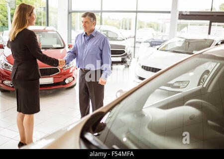 Person shaking hands in front of a car - Stock Photo