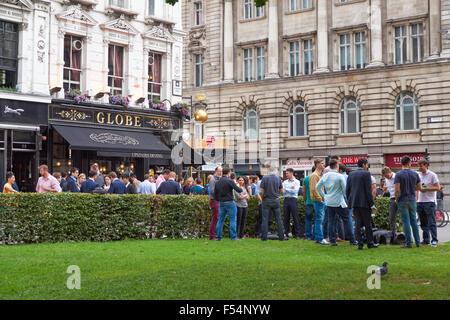 People drinking outside The Globe pub in London England United Kingdom UK - Stock Photo