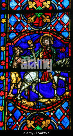 Stained glass window depicting Saint Martin of Tours cuting a piece of his cloak for a beggar in the Cathedral of - Stock Photo