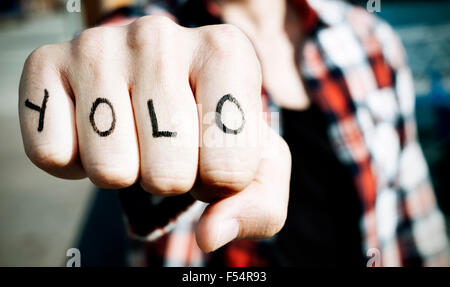closeup of a young man with the word yolo, for you only live once, in his knuckles, with a filter effect - Stock Photo