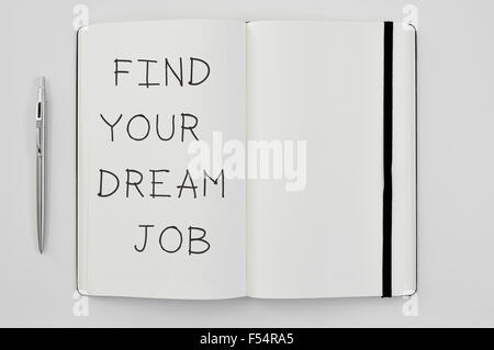 high-angle shot of a pen and a notepad with the text find your dream job written in it - Stock Photo