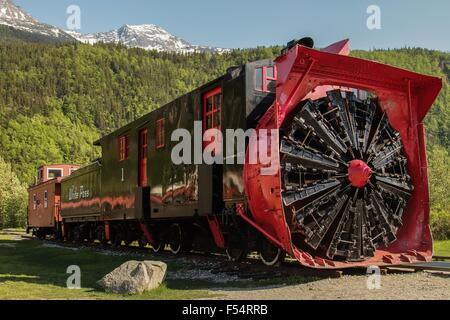Old snow blower train at Skagway Alaska and trees in the background - Stock Photo