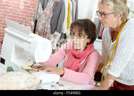 Two cheerful seamstresses working together in their fashion workshop - Stock Photo