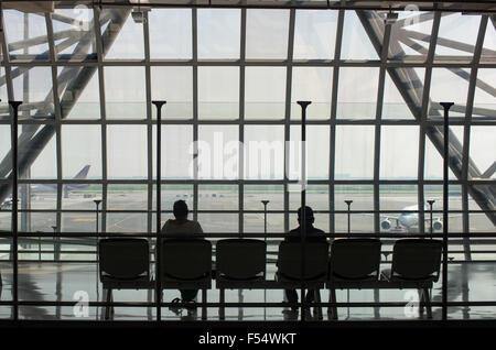 Passengers waiting for their flight at Suvarnabhumi International Airport in Bangkok, Thailand. - Stock Photo