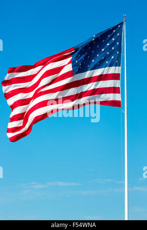 Stars and Stripes American flag blowing in the wind from flagpole on blue sky day in USA - Stock Photo