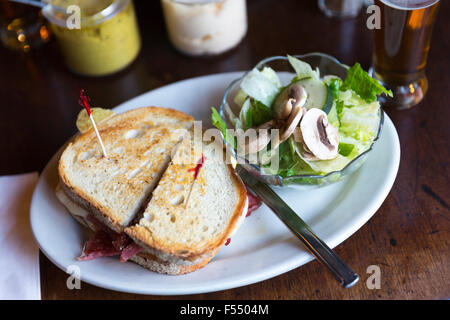 Giant deli bread sandwich with mustard and salad in bar diner restaurant in Soho, New York, USA - Stock Photo