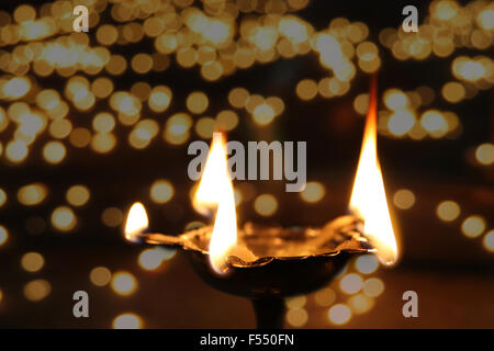A holy ritual lamp lit in temple on the occasion of Diwali festival in India, on the backdrop of other blurred lamps - Stock Photo