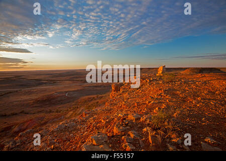 Stunning Australian outback landscape from hilltop lookout at sunset, rocky mesas on vast barren treeless plains - Stock Photo