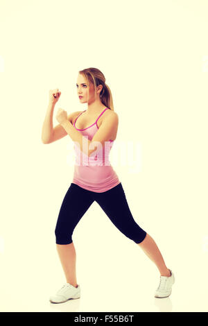 Young woman in kick fitness pose. - Stock Photo