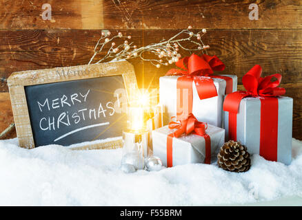 Closeup of Christmas gifts with candle and slate. - Stock Photo