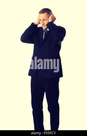 Tired man covering ears with hands - Stock Photo