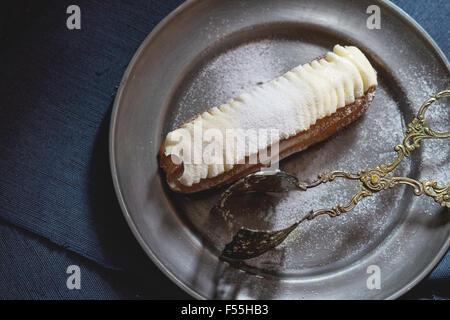 Eclair in metal plate - Stock Photo