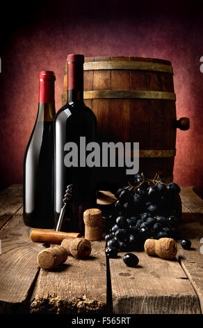 Bottles of wine, corks, corkscrew and wooden cask on table - Stock Photo