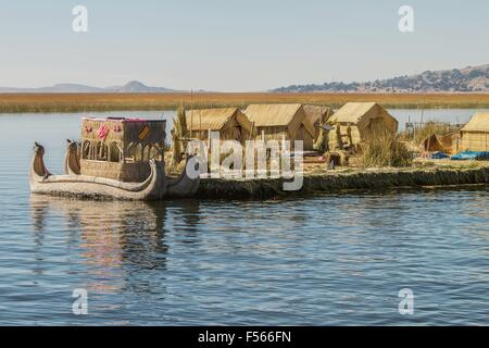 View of floating island Uros, Lake Titicaca, Peru, Bolivia and reed boat with its reflection. - Stock Photo