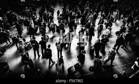 A crowd of people waiting in front of the timetable in London Kings Cross station for a train, London, UK - Stock Photo